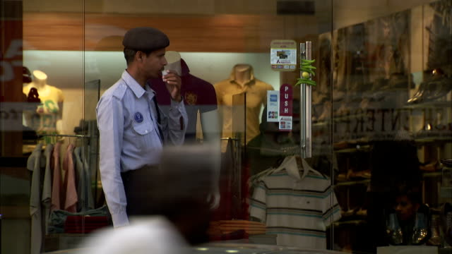 A man in uniform drinks from a paper cup outside a clothes shop in Jaipur, India.