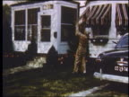 1951 man in workclothes lifting child into air in yard as wife exits house to greet him / Detroit