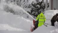 Man in yellow safety suit snowblowing sidewalk and street - medium