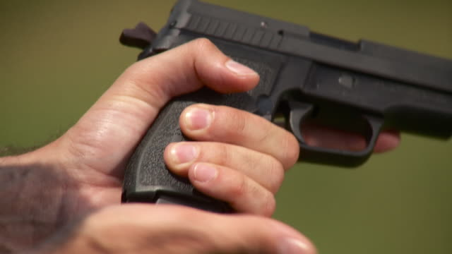 CU Man inserting magazine into 44 caliber handgun, Stowe, Vermont, USA