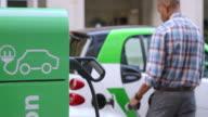 SLO MO Man inserting plug into car at charging station