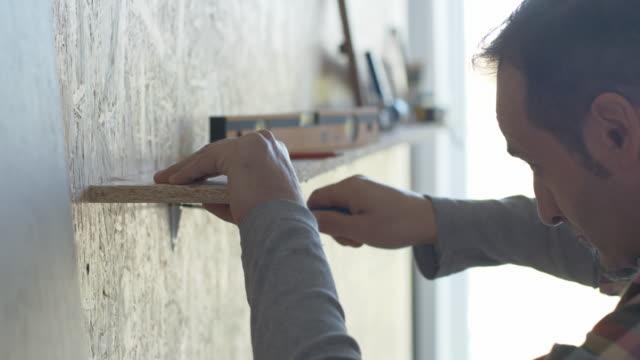 Mann, die Installation einer Werkzeug-rack an eine Wand