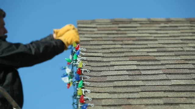 Man Installing LED Christmas Lights onto a House Roof