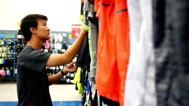 man is choosing clothes at sport department