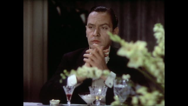 Man (Fredric March) is roused by the applause in a crowded dining room