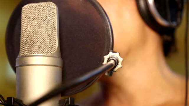 man is singing in a recording studio