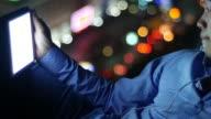 Uomo utilizzando smartphone con luci bokeh sfondo