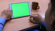 Man is using tablet with green screen on the wooden table