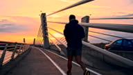 SLO MO Man Jogging Across A Bridge At Dusk