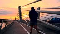 SLO MO, Mann Joggen auf einer Brücke in der Abenddämmerung