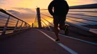SLO MO Man Jogging Across A Bridge