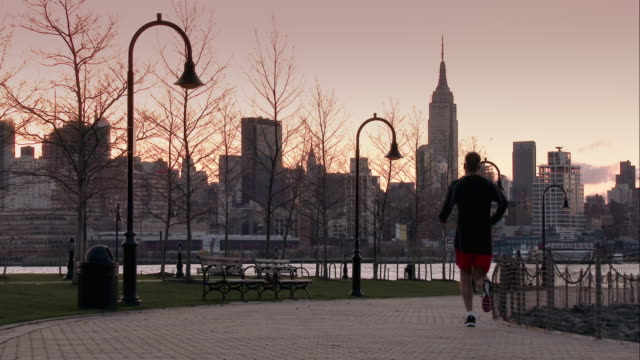 Man Jogging Along a Hoboken Park Path Overlooking Midtown Manhattan and the Hudson River