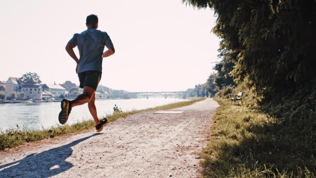 SLO MOTION uomo jogging sul fiume in città