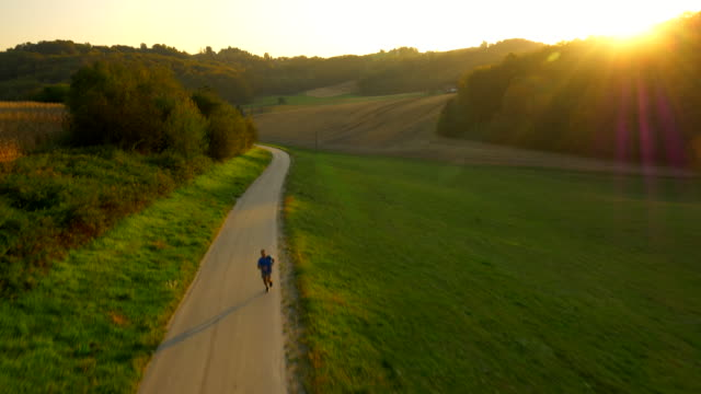 AERIAL Man Jogging In The Countryside At Sunset