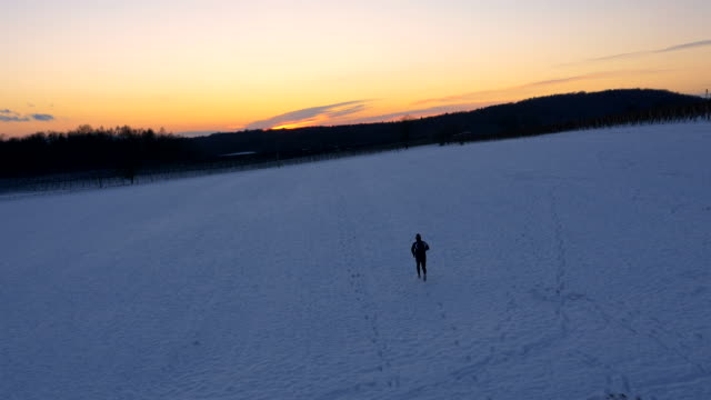 AERIAL Man Jogging In Wintry Countryside