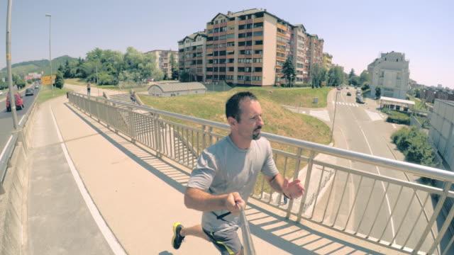 POV uomo jogging su un ponte