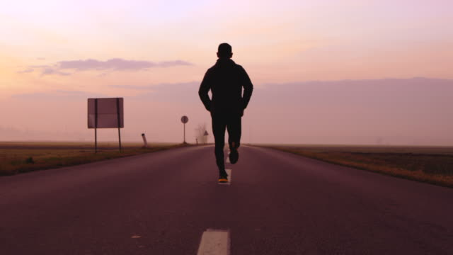 SLO MO Man jogging on a country road at sunset