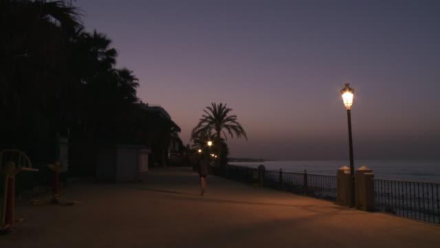 MS Man jogging on walkway at early morning / Malaga, Andalusia, Spain