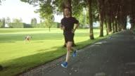 SLO MO TS Man jogging through a beautiful avenue in the park