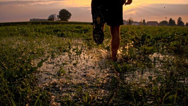 SLO MO Man Jogging Through Puddles At Sunset
