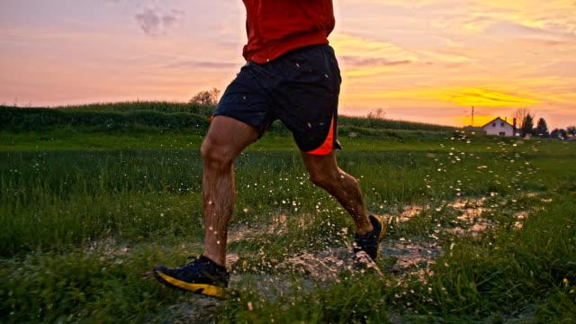 SLO, MO, Mann, Jogging durch Pfützen zu waten