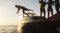 SLO MO Man jumping into the water from a party boat at sunset