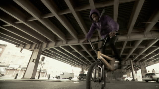 WS LA SLO MO Man jumping on BMX bicycle under overpass, Brooklyn, New York City, New York State, USA