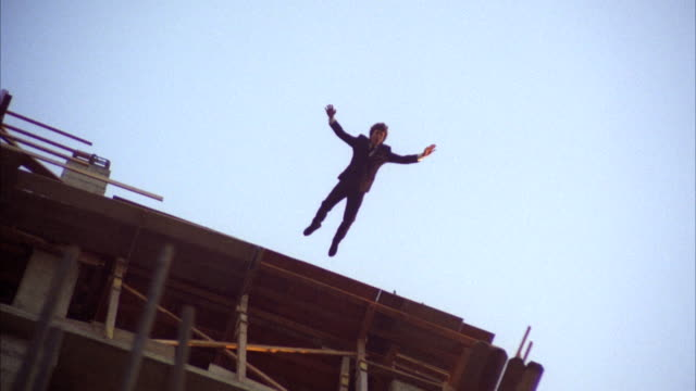 MS ZI Man jumping to roof of eleven story under construction building / Los Angeles, California, United States
