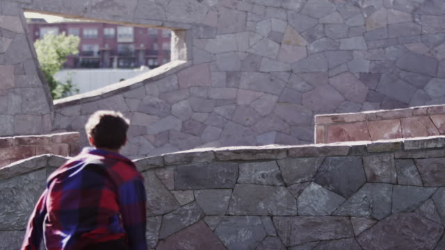 MS SLO MO Man jumps over a stone wall and then does flip / Denver, Colorado, United States