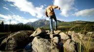 Man jumps rock to rock in mountain lake