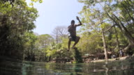 Man jumps to the water with a liana. Low point of view. A wave goes to camera. Natural swimming pool of Ojo de Agua. Ometepe, Nicaragua.