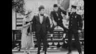 Fatty Arbuckle kicks policeman in behind and blames jealous mean man who is taken away by police