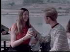 MS, Man kissing woman on cheek and sharing beer can sitting at picnic table, West Covina, California, USA