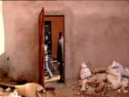 Man leads donkey and cart past open door in wall