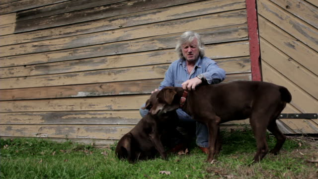WS ZO Man leaning against barn with his dogs / Kingston, New York, USA