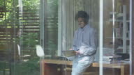 MS man leaning against desk in glass walled home office writing on notepad looking out window and walking out of office