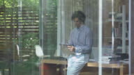 MS DS R/F man leaning against desk in glass walled home office writing on notepad looking out window and walking out office