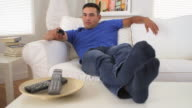 man leaning back and watching TV