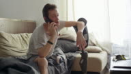 Man leaning elbow on his prosthetic leg and talking on phone