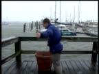 Man leans into wind on marina jetty Hurricane Frances Fort Pierce Florida 4 Sep 2004