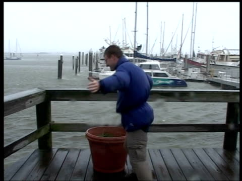 Man leans into wind on marina jetty Hurricane Frances Fort Pierce Florida 4 Sep 2004