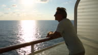 Man leans on ship railing, looks off to sea