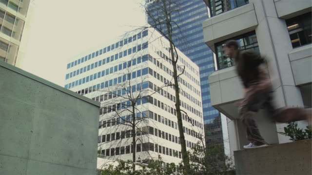 MS Man leaping onto building ledge, performing parkour, Vancouver, British Columbia, Canada