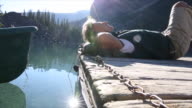 Man lies on wooden lake pier, relaxes besides canoe