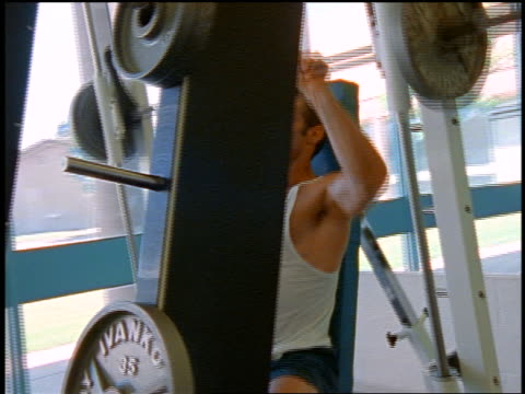 Man lifting barbell above head on weight machine by window in gym / NYC