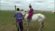 Man lifts boy onto horse, Inner Mongolia, China