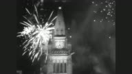 Man lights giant flame with torch on Parliament Hill signaling start of Canada's centennial celebrations / fireworks explode behind Peace Tower /...