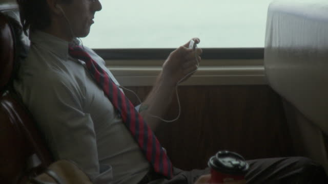 MS TD TU Man listening music on portable media player and drinking coffee in moving commuter train / New York City, New York, USA
