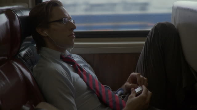MS Man listening music on portable media player in moving commuter train / New York City, New York, USA