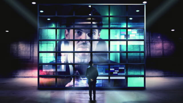 CGI WS Man listening to man talk during video conference, standing in front of large screens
